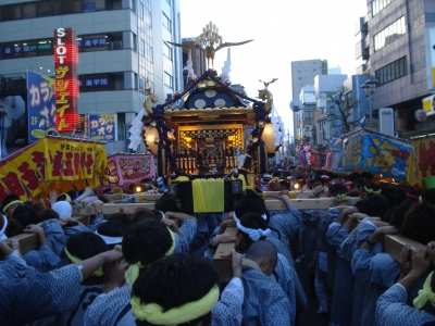 Festival goers parade their neighborhood\'s mikoshi around town on a hot and humid day.
