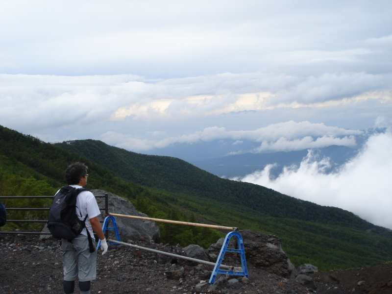 A climber stops to take a look at the view.  This isn't far up Mt. Fuji, but you are already above the clouds.