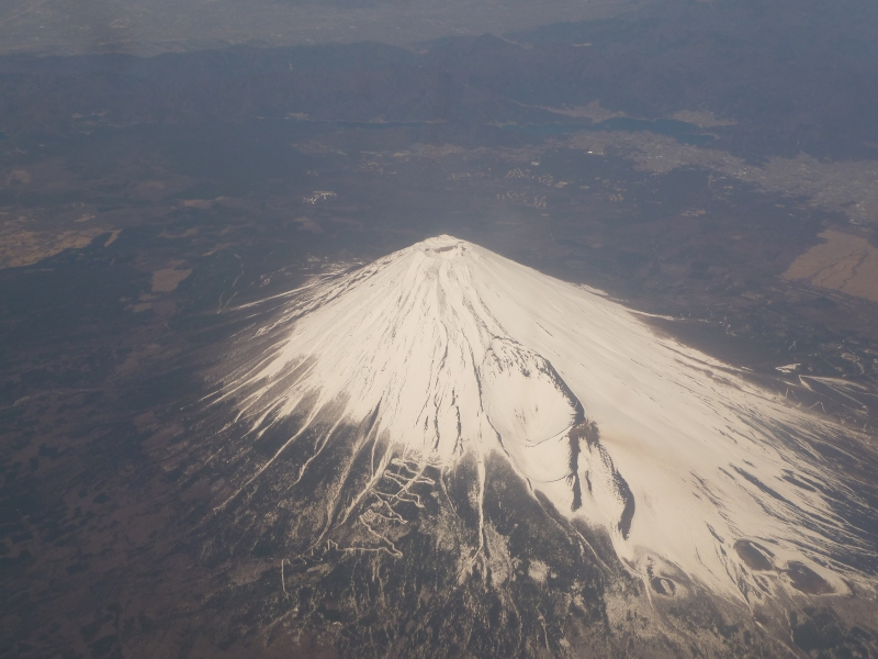 I got lucky and flew right over Mt. Fuji one day in early spring.  You can see the tracks leading up it if you look closely.